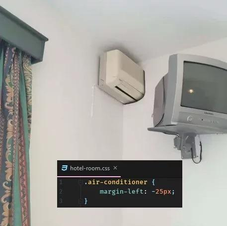 "An air conditioner partially inserted in an adjacent wall, with ""margin-left: -25px"" overlaid on top of the photo."