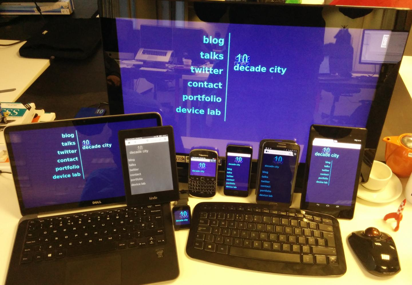 A variety of mobile devices, plus a laptop and a big desktop monitor, all displaying the same website and all having touch capability.