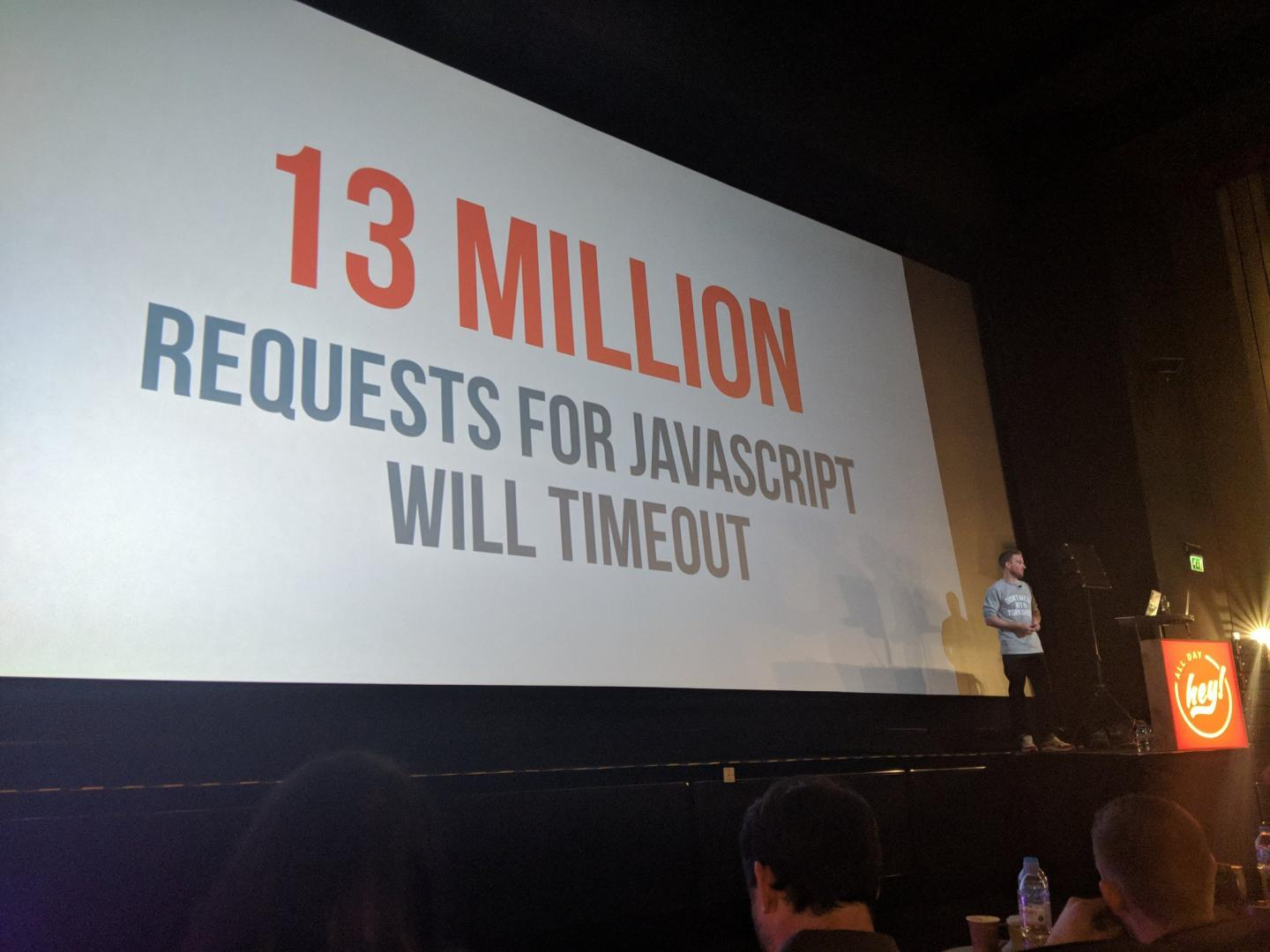 "Ian Feather standing on a stage in front of a graphic that reads ""13 million JavaScript requests will fail""."